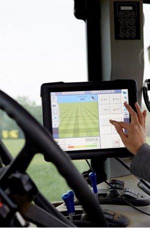 A hand using a digital interface inside a farming vehicle