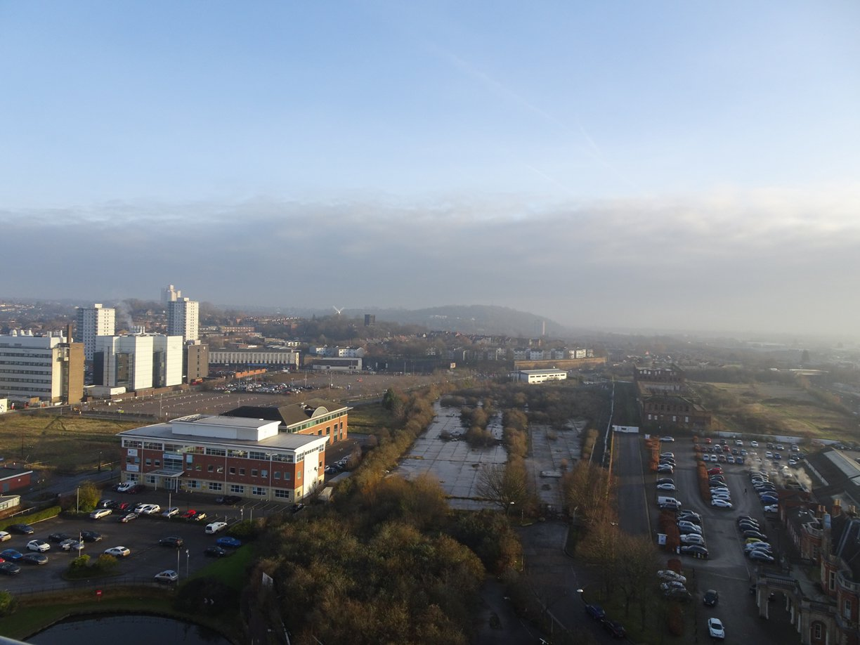 An aerial photograph of office blocks and a car park and derelict land