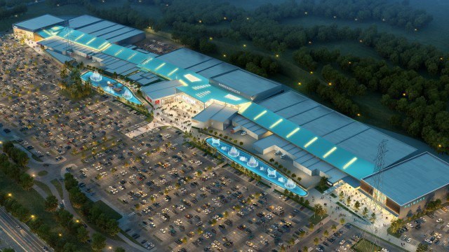 Artistic impression of a new regional shopping centre at night with a full car park at the front