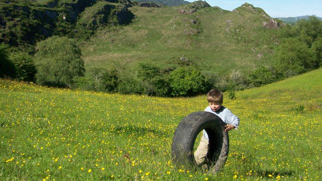 Small boy pushing at Mishergas pushing a tyre up a hill.