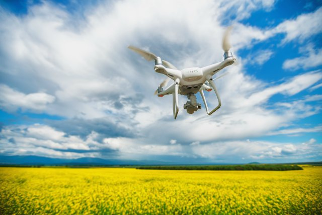 Image of a drone with camera and sensors flying over a field of rapeseed in flower.