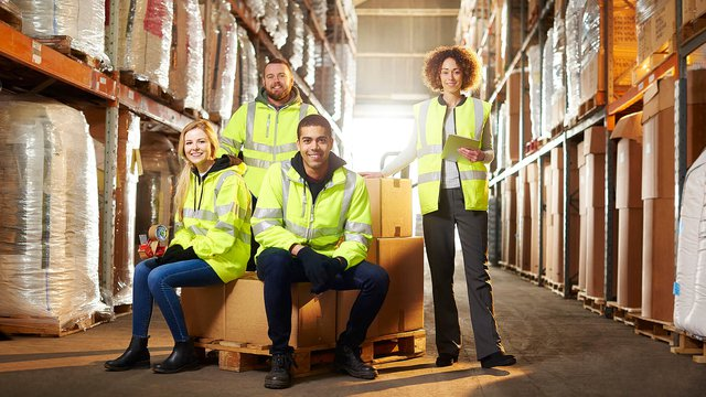 Group of people wearing high-vis jackets in a warehouse